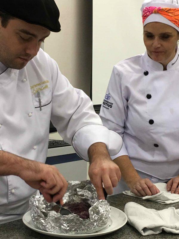 O chef Hermes Custódio, com a supervisão de Josete Leprevost, abrindo o papilotte de salmão